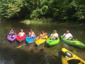 family in kayaks in river