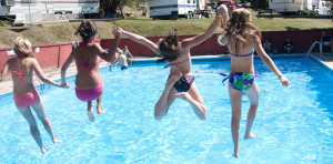 young girls jumping in swimming pool
